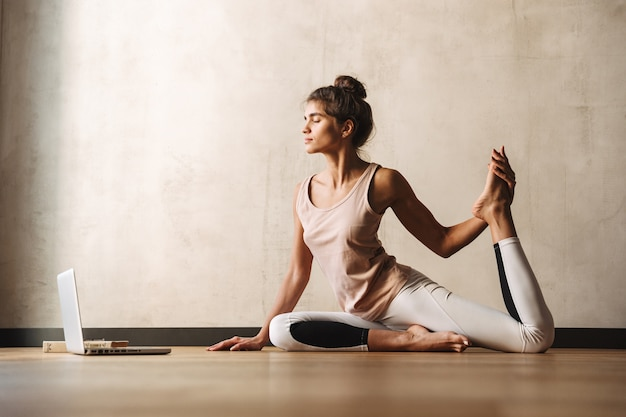 Photo of young concentrated woman in sportswear doing yoga exercises using laptop while sitting on floor at home