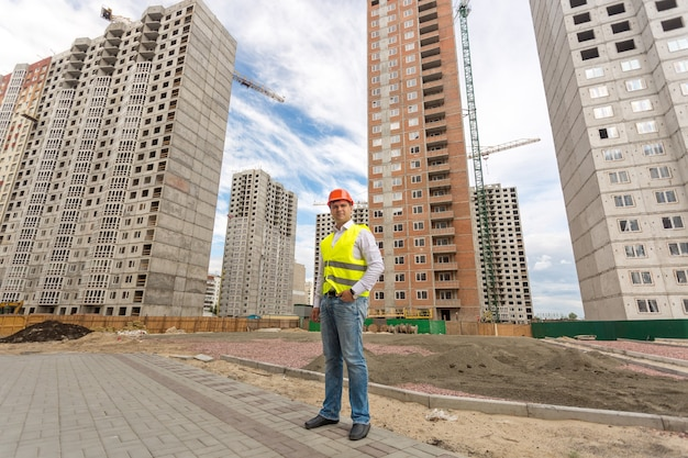 Photo of young construction engineer standing in front of buildings under construction