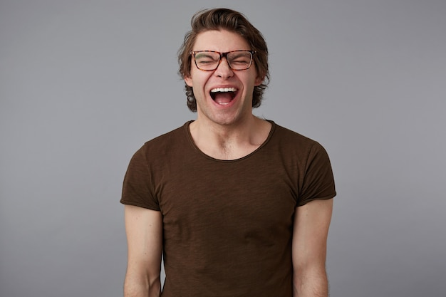 Photo of young crying guy with glasses wears in blank t-shirt, stands over gray background and looks unhappy and sad.