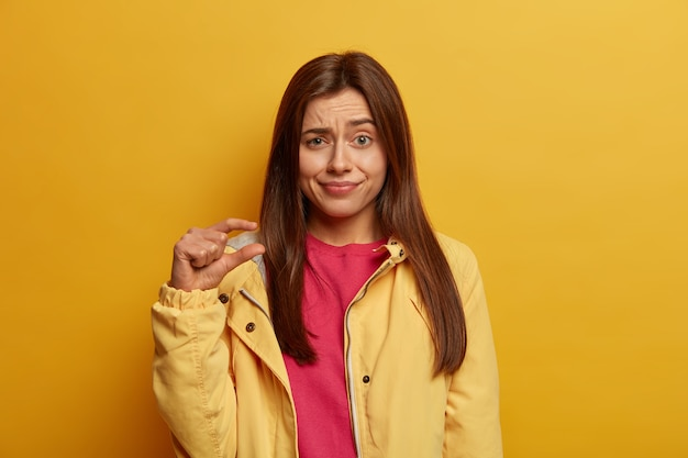 Photo of young dark haired woman shows very small size with fingers, demonstrates tiny measure, tells about decreased prices and little salary, raises eyebrows with bewilderment, wears yellow jacket