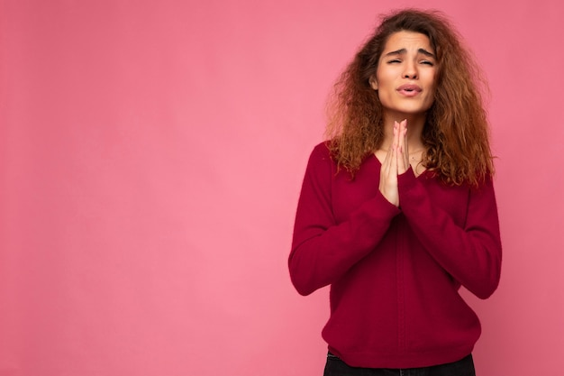 Photo of young emotional beautiful brunette curly woman with sincere emotions wearing trendy pink