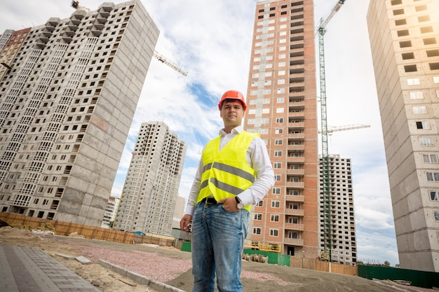 Photo of young engineer in hardhat against construction site