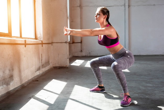 Photo of a young fitness woman standing in the gym near the window while doing sports exercises