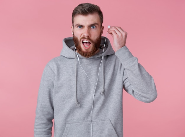 Photo of young frowning handsome red bearded man in gray hoodie, one earpiece stopped working, disapprovingly looks at camera wit raised eyebrows, stands over pink background.