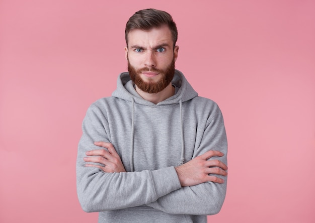 Photo of young frowning handsome red bearded man in gray hoodie, stands with crossed arms, disapprovingly looks at camera wit raised eyebrow ,stands over pink background.