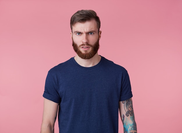 Photo of young frowning tattooed misunderstanding red bearded man in blank t-shirt, stands over pink background, looks at the camera.