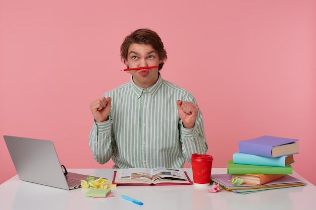 Photo of young funny guy with glasses, sitting at a table with books, working at a laptop, looks up and holds pencil at the lips, with up fists, isolated over pink background.