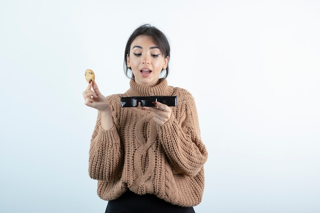 Photo of young girl eating chip cookies on white background.