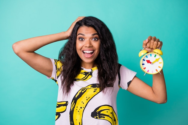 Photo of young girl hold alarm clock hand head open mouth wear banana print t-shirt isolated teal color background