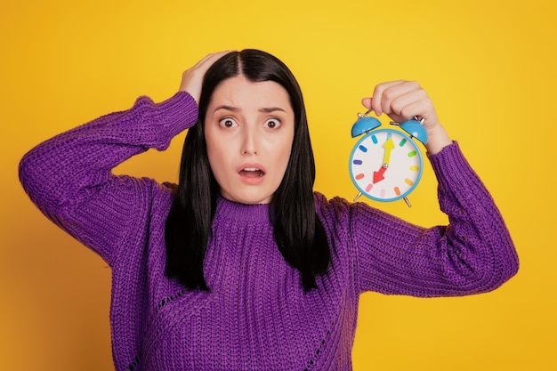 Photo of young girl shocked surpised deadlinehand touch head hold clock alarm timer isolated over yellow color background