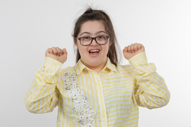 Photo of young girl with a down syndrome wearing yellow checkered shirt posing