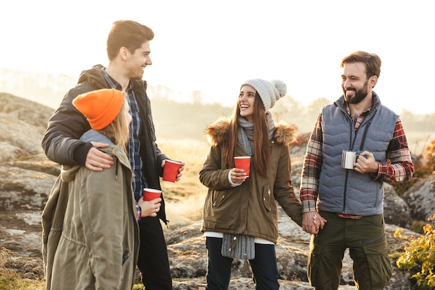 Photo of young group of friends outside in free alternative vacation camping over mountains drinking hot tea talking with each other.