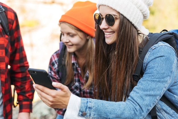 Photo of young group of friends outside in free alternative vacation camping over mountains using mobile phone, focus on girl.
