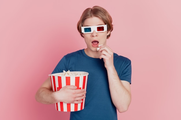 Photo of young guy amazed shocked eat popcorn wear 3d glasses watch movie isolated pink color background