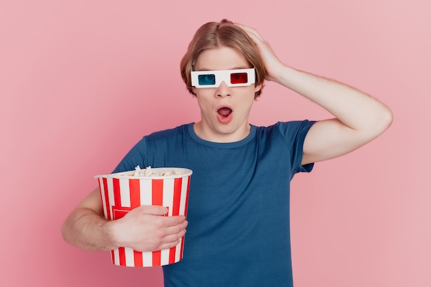 Photo of young guy hold popcorn paper box wear 3d glasses amazed shocked surprised watch thriller isolated pink color background
