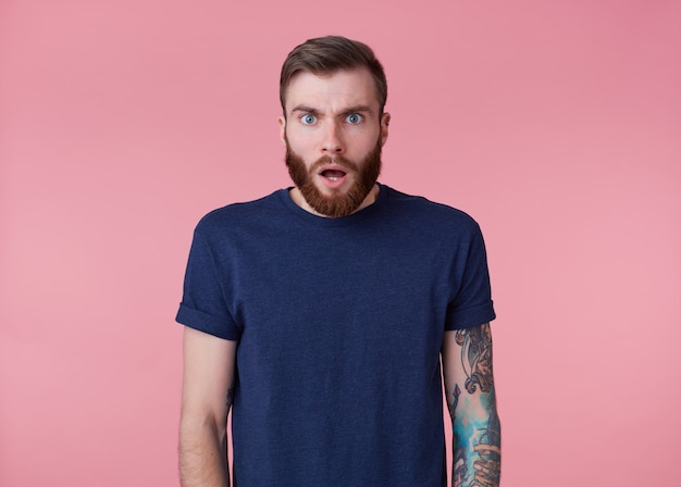 Photo of young handsome amazed red bearded manman in blank t-shirt, hears unbelievable news, looks surprised, stands over pink background with wide open mouth and eyes.