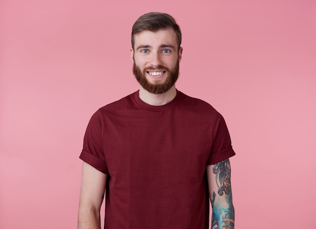 Photo of young handsome cheerful red bearded man in red t-shirt, looks happy and broadly smiles, stands over pink background.