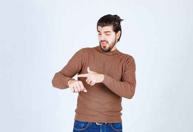 Photo of a young handsome man model standing and pointing at his hand . high quality photo