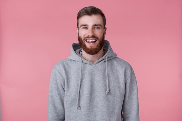 Photo of young handsome positive red bearded man in gray hoodie, looks happy and broadly smiles, stands over pink background.