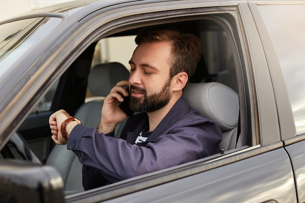 Photo of young handsome successful bearded man in a blue jacket and striped t-shirt, sits behind the wheel of the car, calls on mobile phone, looks at his watch to plan a meeting.