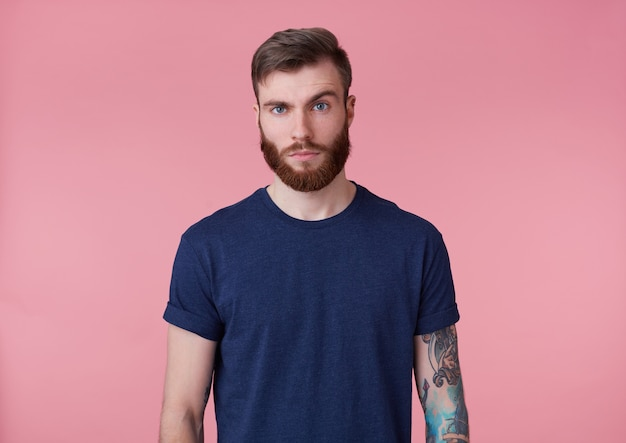 Photo of young handsome tattooed misunderstanding red bearded man in blank t-shirt, stands over pink background, looks at the camera with raised eyebrow.