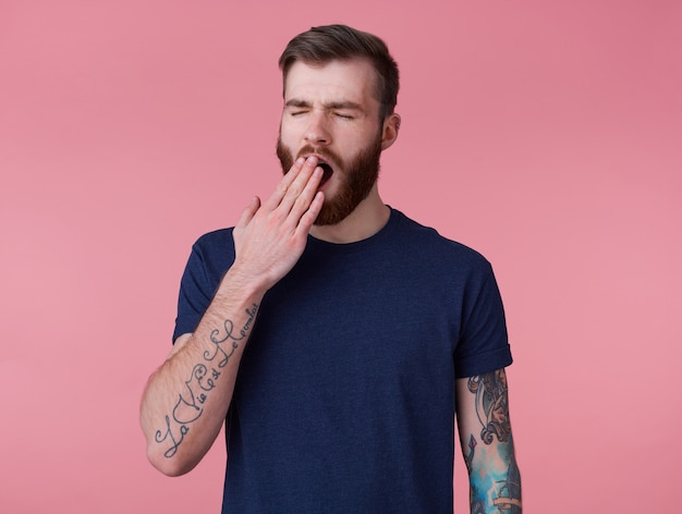 Photo of young handsome tired red bearded manman in blank t-shirt, wonts to sleep and yawns, stands over pink background with wide open mouth and eyes.
