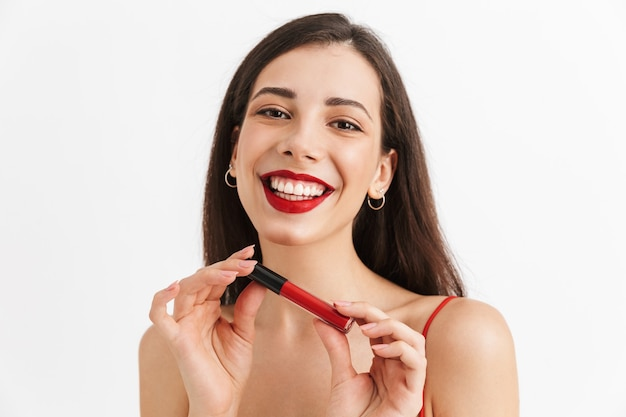 Photo of young happy excited woman posing isolated holding lip gloss doing makeup.