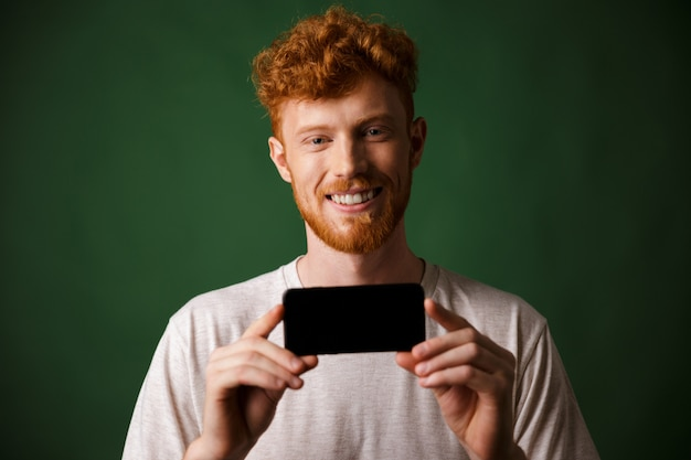 Photo of young happy redhead bearded man in white tshirt makes a photo on smartphone mobile