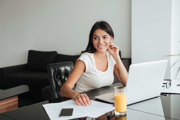 Photo of young happy woman using laptop and analyzing home finances. look aside.