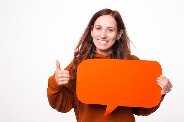 Photo of a young joyful woman smiling at the camera showing a thumb up and holding a speech bubble