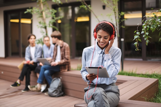 Photo of young lady sitting on bench in red headphones and tablet in hands while spending time in courtyard of university