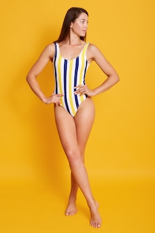Photo of and young lady in stylish striped swimsuit, keeping hands on hips ands lookingt aside, model with long slim legs posing isoalted on yellow.
