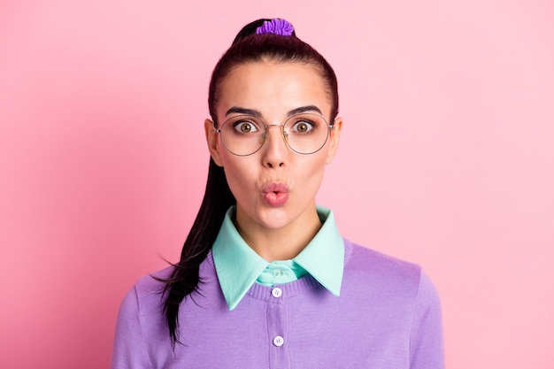 Photo of young lady tail hairdo look camera lips wear specs purple cardigan isolated pink color background