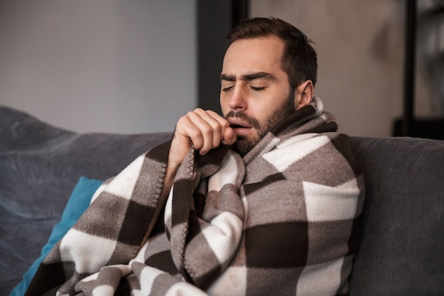 Photo of young man 30s wrapped in blanket having temperature and looking sick while sitting on sofa in apartment