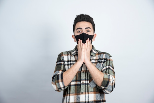 Photo of young man in black mask for protection coronavirus standing over white wall. Free Photo
