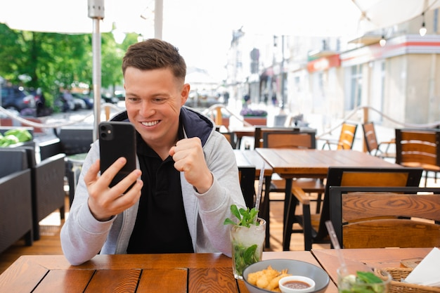 Photo of young man, blogger, sits at table in street cafe and records video on smartphone