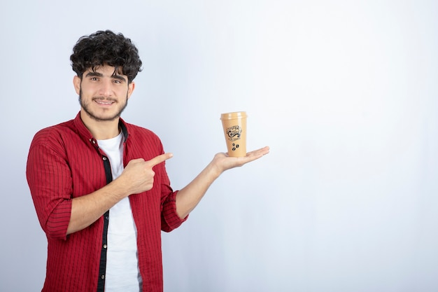 Photo of young man in casual outfit pointing at cup of coffee on white background. high quality photo