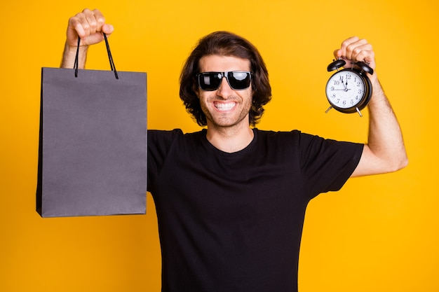Photo of young man demonstrate hold alarm clock timepiece dial store package t-shirt sunglass isolated yellow color background