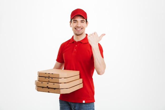 Photo of young man from delivery service 25y in red uniform carrying stack of pizza boxes and pointing finger aside on copyspace, isolated over white space
