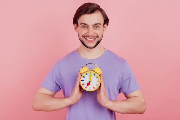 Photo of young man happy positive smile hold clock alarm time timer isolated over pastel color background