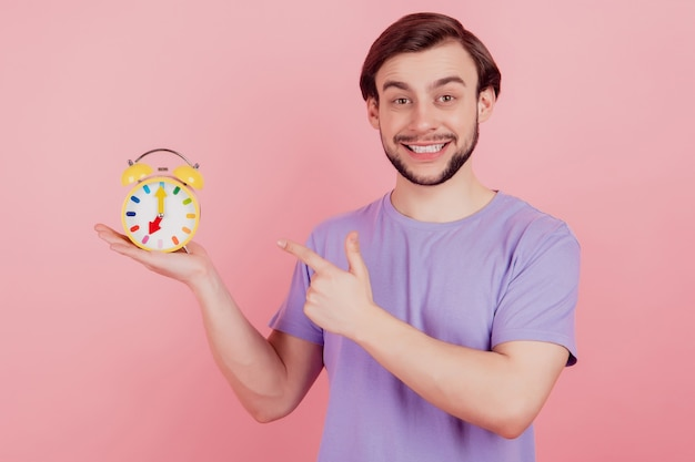 Photo of young man happy positive smile point finger clock alarm late isolated over pastel color background