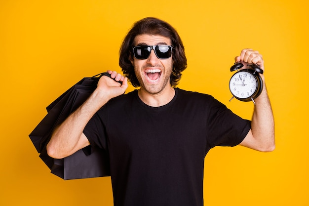 Photo of young man hold alarm clock many shop packages t-shirt sunglass isolated yellow color background