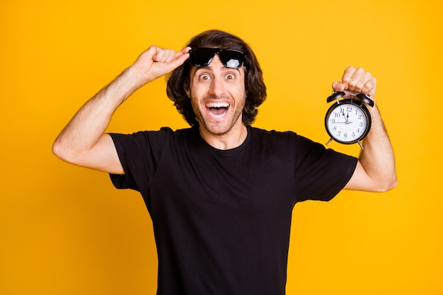 Photo of young man hold alarm clock show dial take off glasses wear t-shirt sunglass isolated yellow color background