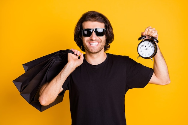 Photo of young man hold mall bags alarm clock toothy smile wear black t-shirt sunglass isolated yellow color background