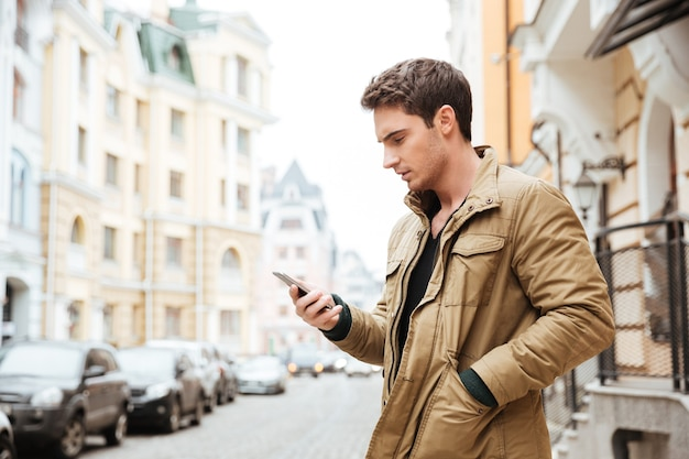 Photo of young man walking on the street and chatting by his phone outdoors. look at phone.