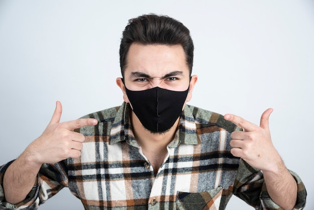 Photo of young man wearing black mask for protection over white wall.