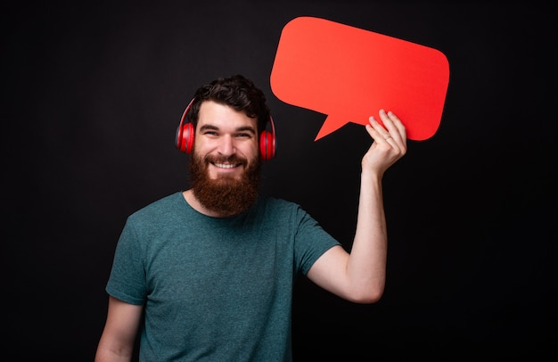 Photo of young man with beard listening music at red headphones and holding red speech bubble