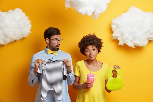Photo of young married couple prepare for becoming parents, pose with newborn wear, bib and feeding bottle, isolated on yellow . future father and mother expect child. parenthood, pregnancy