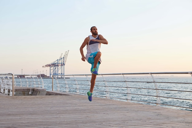 Foto di giovane ragazzo di salto con la barba sportivo maschile che fa stretching, esercizi mattutini in riva al mare, riscaldamento dopo la corsa.