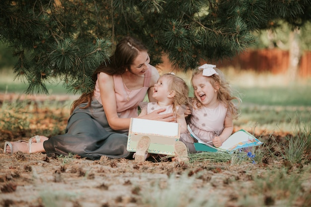 Photo of young mother with two cute kids reading book outdoors in spring time, happy mom teaching her children in the park, happy family, mom and two daughters. mother's day concept